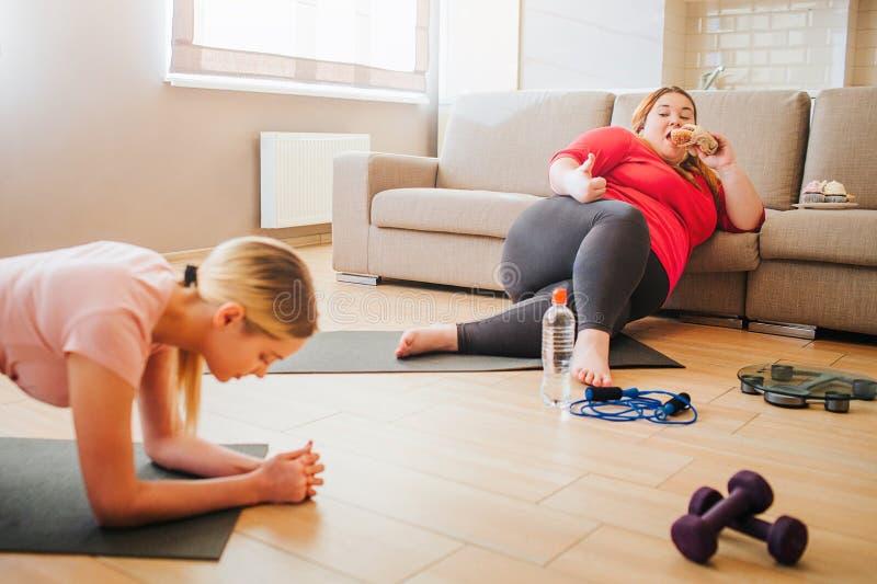 Corte la vista de la situación delgada joven de la mujer en la posición del tablón Modelo positivo del cuerpo gordo que se inclin imagenes de archivo