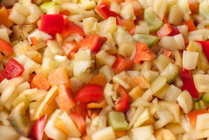 Corte los pedazos de las rebanadas de paprika dulce rojo, amarillo y verde imágenes de archivo libres de regalías