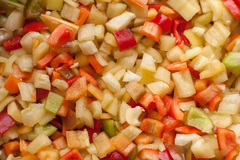 Corte los pedazos de las rebanadas de paprika dulce rojo, amarillo y verde foto de archivo