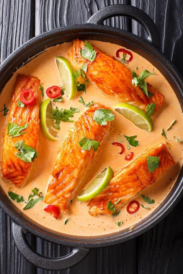 Corte los salmones en salsa tailandesa picante del coco con la cal y el primer de las hierbas en una cacerola Visi?n superior ver foto de archivo