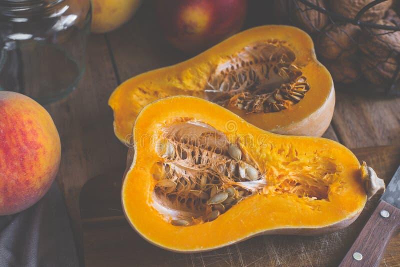 Corte na meia abóbora madura da polpa de butternut na placa de corte de madeira Pêssegos, nectarina, porcas, ingredientes crus do fotografia de stock