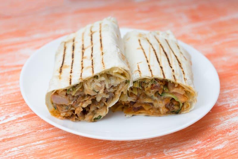 Corte no meio rolo fresco de Shawarma do sanduíche com lavash, galinha grelhada, cogumelos, molho, pepinos, couve imagens de stock royalty free