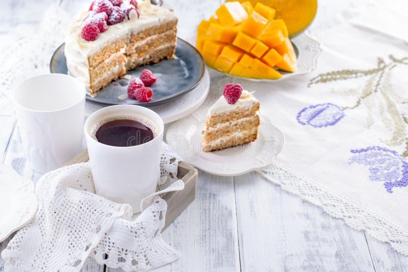 Corte o bolo com creme branco, para o fruto da manga do café da manhã A O fundo branco, toalha de mesa com laço, uma xícara de ca foto de stock