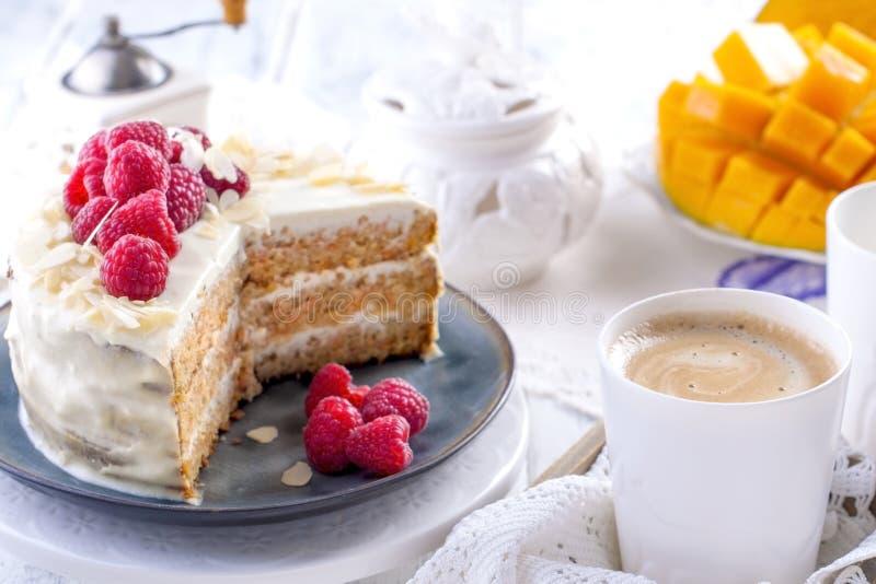 Corte o bolo com creme branco, para o fruto da manga do café da manhã A O fundo branco, toalha de mesa com laço, uma xícara de ca imagens de stock royalty free