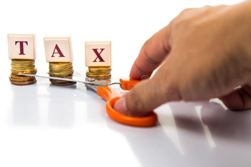 Corte o conceito dos impostos com moedas e tesouras imagem de stock
