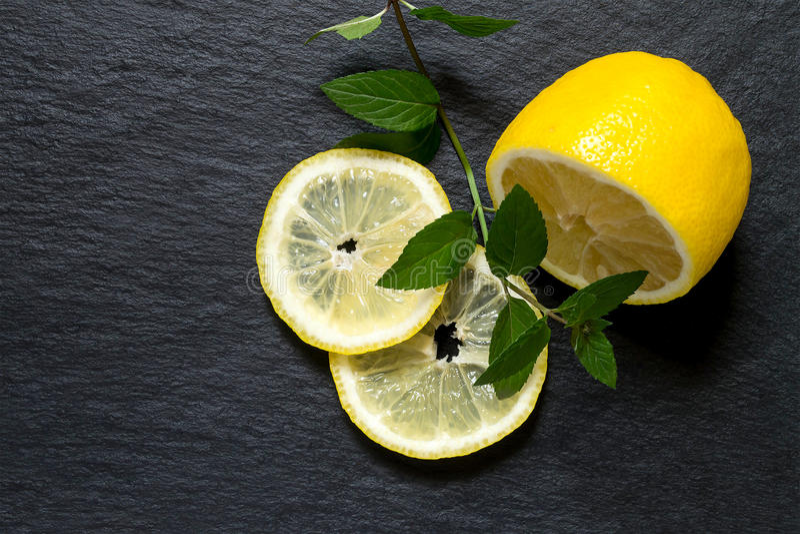 Corte o limão com um ramo da hortelã em um quadro-negro da ardósia fotos de stock royalty free