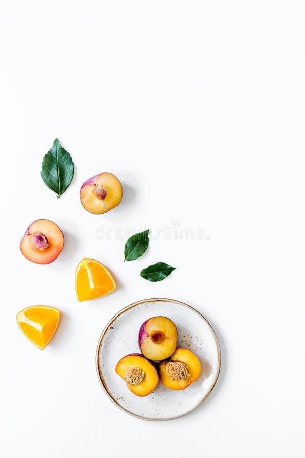 Corte o pêssego e a laranja para o fruto exótico no modelo branco da opinião superior do fundo das placas imagens de stock