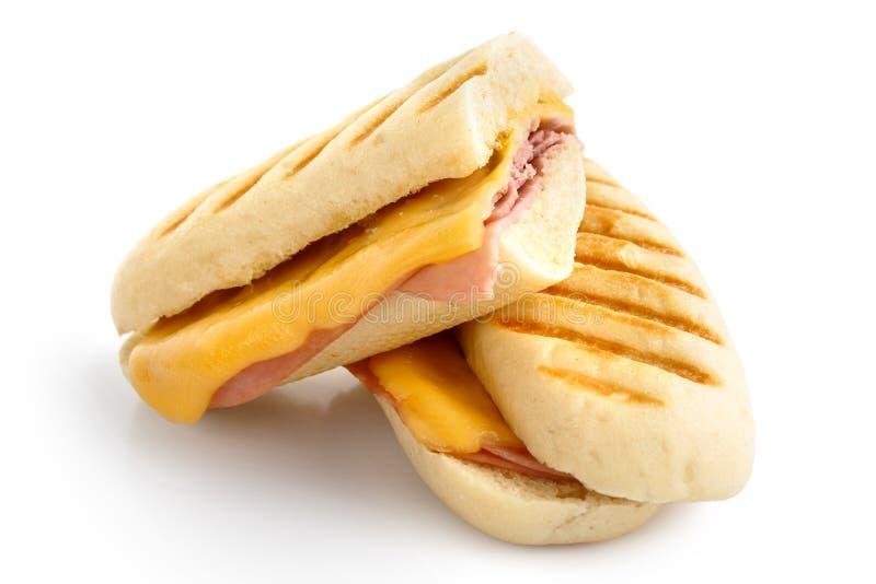 Corte o queijo e o derretimento brindado presunto do panini Isolado no branco foto de stock royalty free