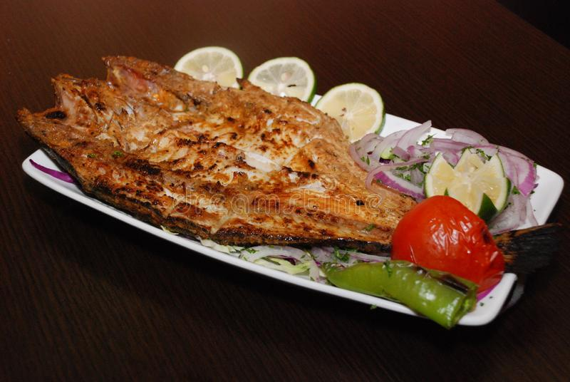 Corte peixes com salada, fatias do cal, anéis de cebola frescos na placa branca foto de stock royalty free