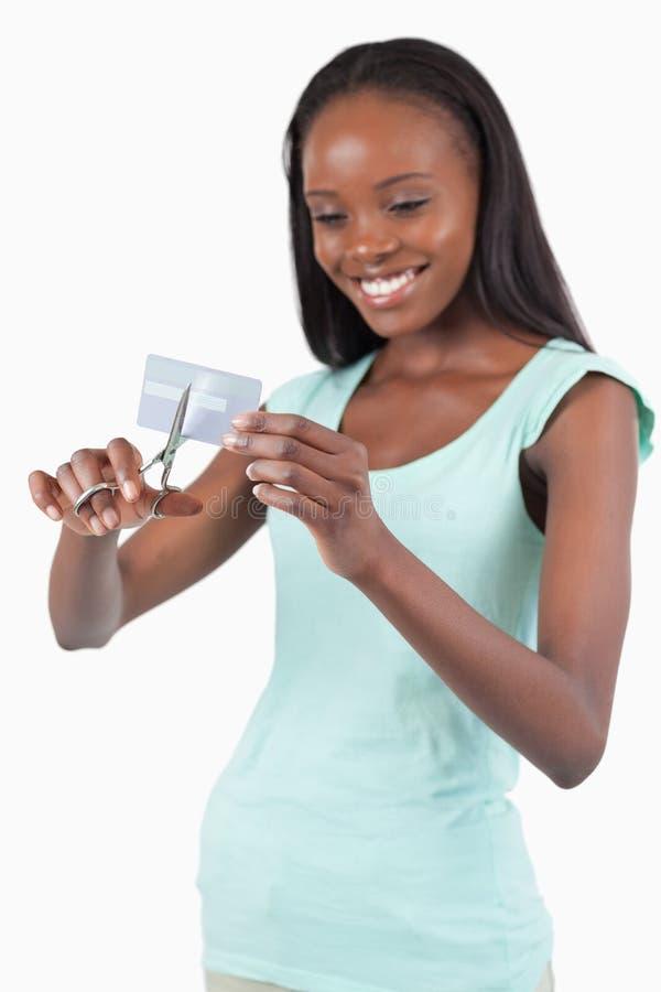 Corte sonriente de la mujer ella de la tarjeta de crédito en pedazos imágenes de archivo libres de regalías