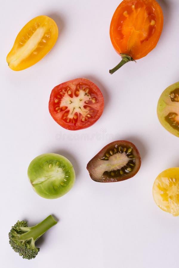 Corte tomates e brócolis da cor no branco foto de stock royalty free