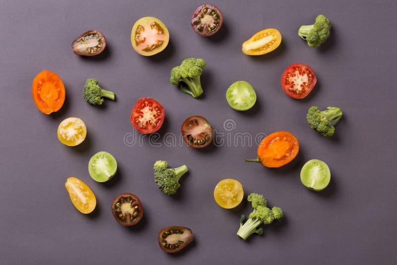 Corte tomates e brócolis no fundo cinzento imagens de stock