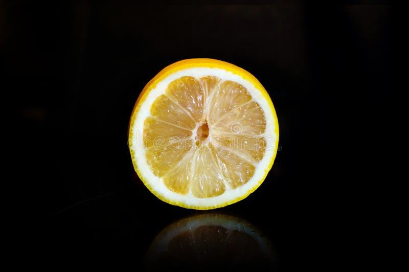 Corte un limón maduro aislado en fondo negro fotografía de archivo libre de regalías