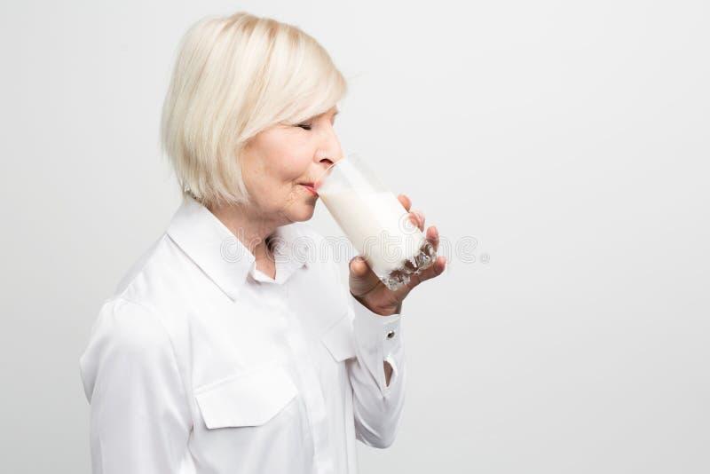 Corte a vista da posição loura e de beber da mulher um copo do leite orgânico imagem de stock