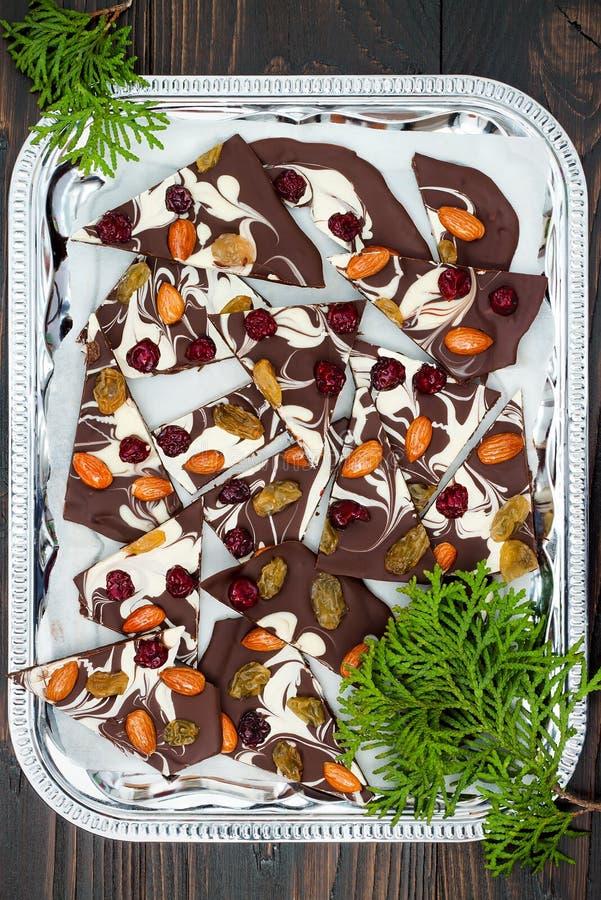 Corteccia del cioccolato di festa con i frutti secchi e dadi su un fondo di legno scuro Vista superiore Ricetta del dessert per l immagine stock
