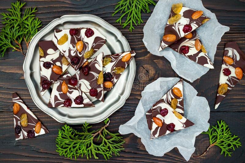Corteccia del cioccolato di festa con i frutti secchi e dadi su un fondo di legno scuro Vista superiore Ricetta del dessert per l fotografie stock libere da diritti