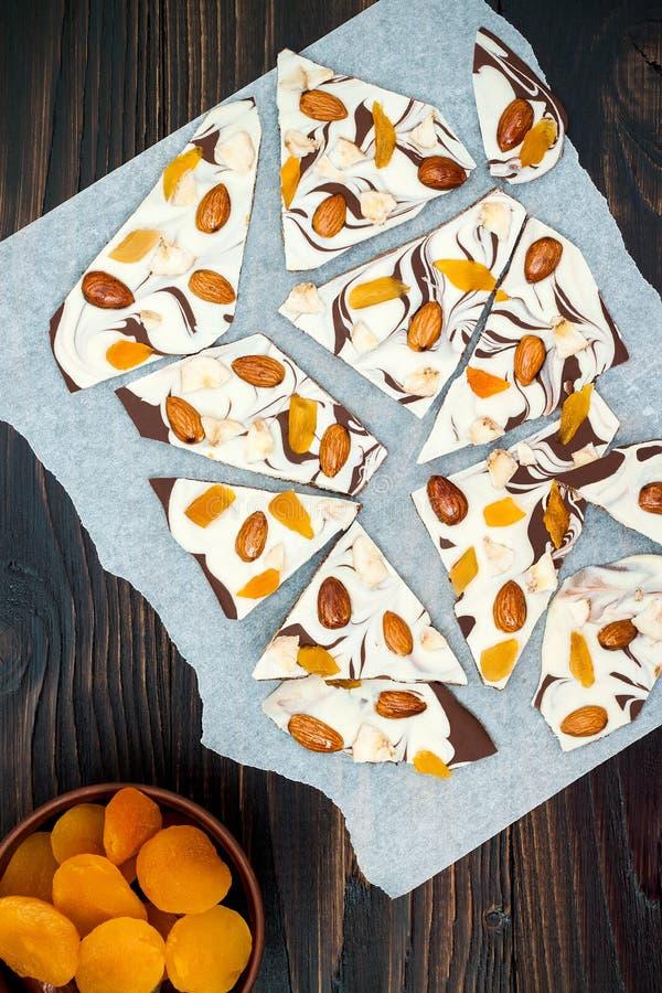 Corteccia del cioccolato di festa con i frutti secchi e dadi su un fondo di legno scuro Vista superiore Ricetta del dessert per l fotografia stock libera da diritti