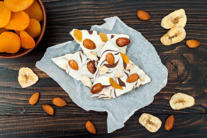 Corteccia del cioccolato di festa con i frutti secchi e dadi su un fondo di legno scuro Vista superiore Ricetta del dessert per l fotografia stock