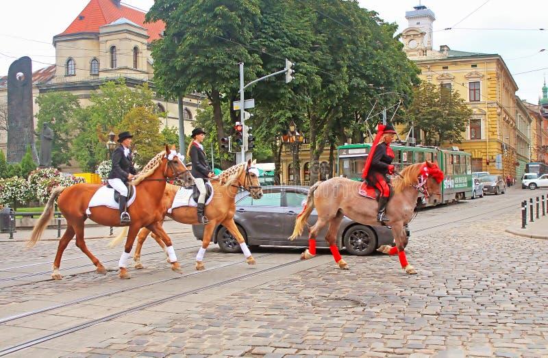Cortege met ruiters op horseback op de straten stock afbeeldingen