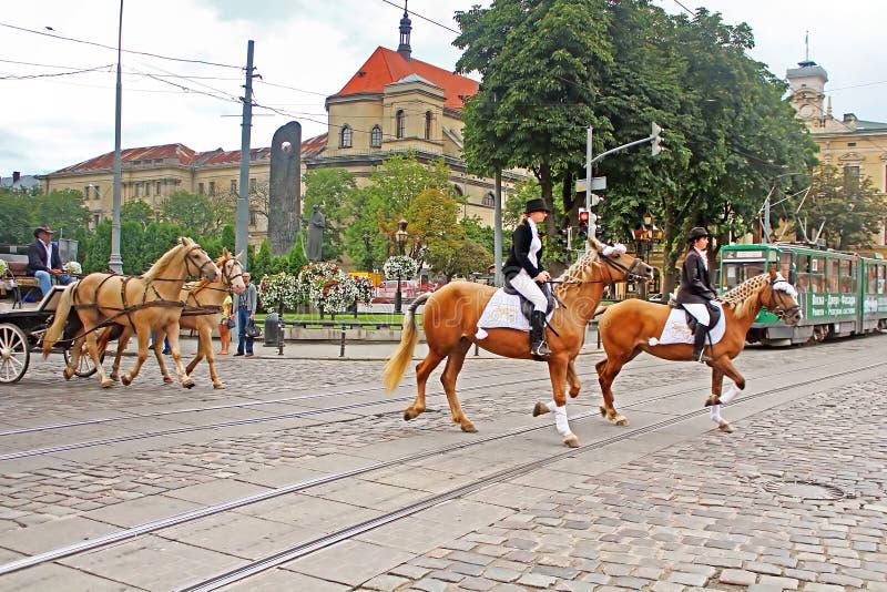 Cortege met ruiters op horseback op de straten in historisch stadscentrum, Lviv royalty-vrije stock foto