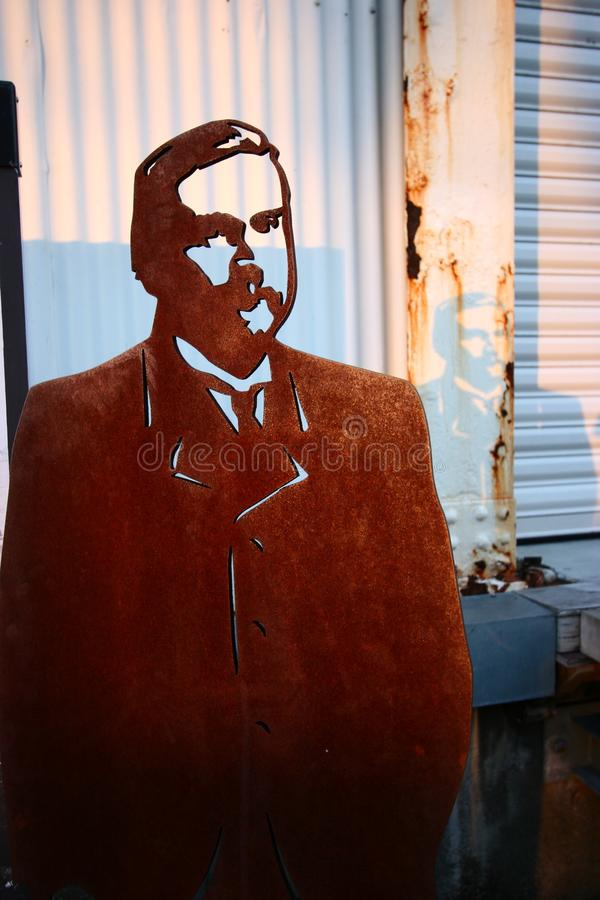 Outdoor historic migrant cutout in rusted corten steel of Many Lovers exhibition at sunset on Queens Wharf, Auckland, New Zealand royalty free stock images