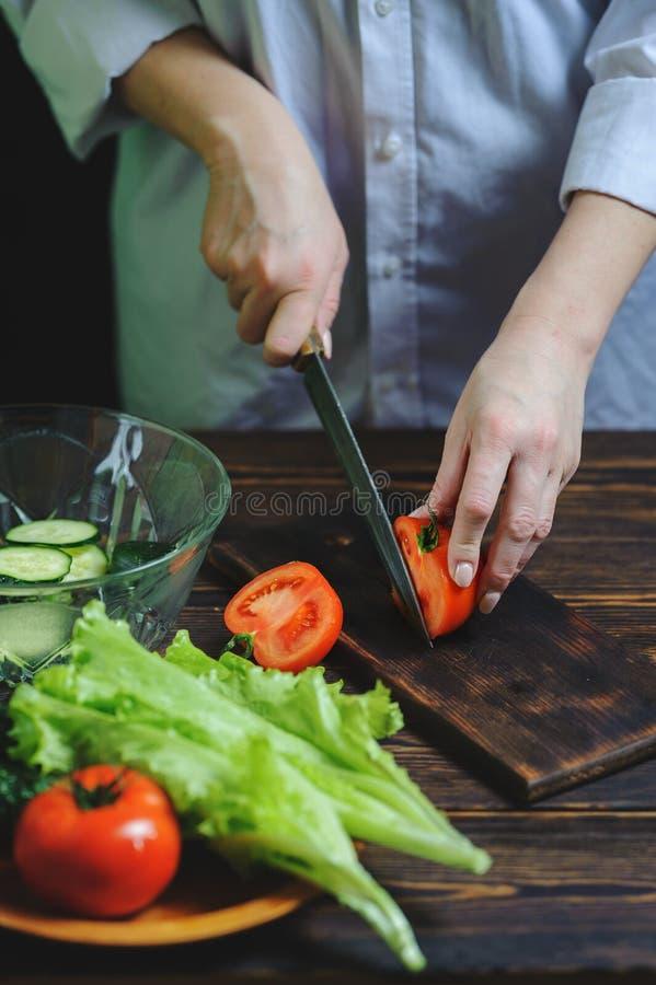 Cortes del cocinero con un cuchillo un primer del tomate fotos de archivo