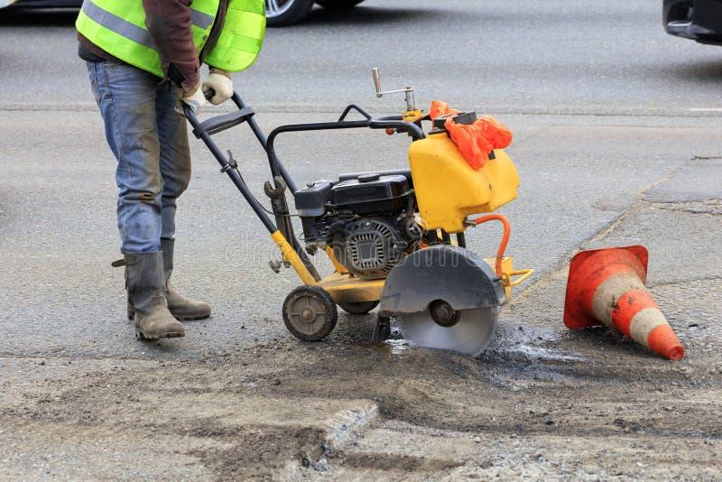 Cortes del trabajador al pedazo de mún asfalto con un cortador de la gasolina durante la construcción de carreteras fotografía de archivo