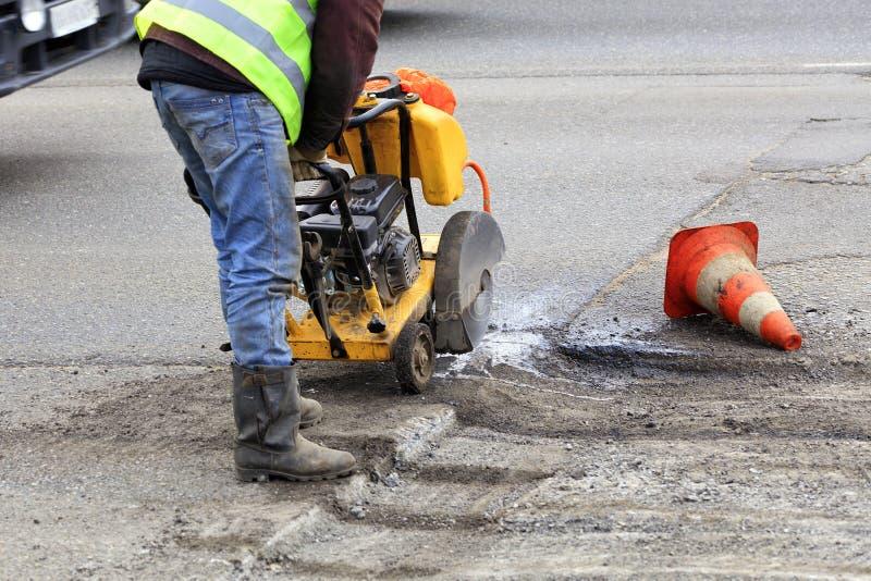 Cortes del trabajador al pedazo de m?n asfalto con un cortador de la gasolina durante la construcci?n de carreteras fotos de archivo libres de regalías