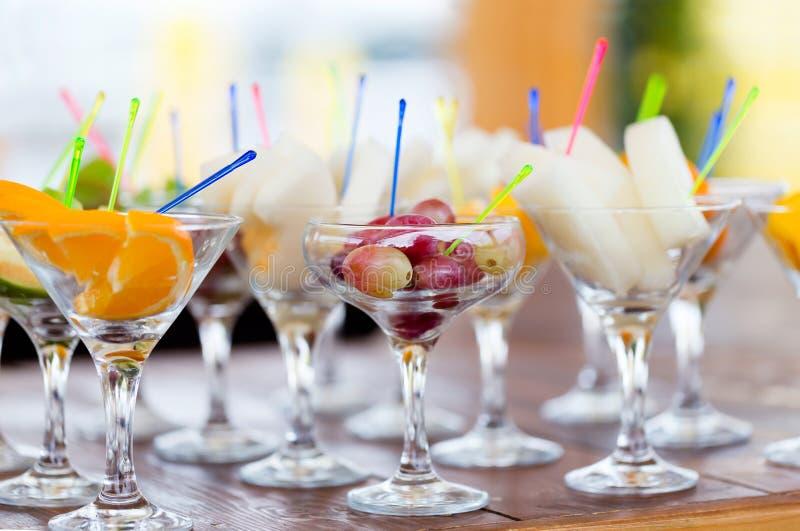 Cortes do fruto fresco em vidros do partido do champanhe imagens de stock
