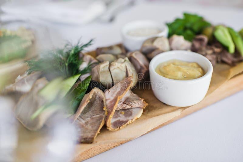 Cortes fr?os en una tajadera de madera Banquete en el restaurante imagenes de archivo