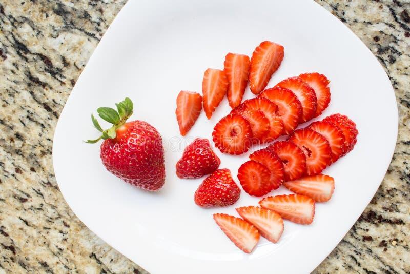 Cortes frescos de la fresa en el plato blanco, fruta deliciosa Postre sano y rico en vitaminas fotografía de archivo