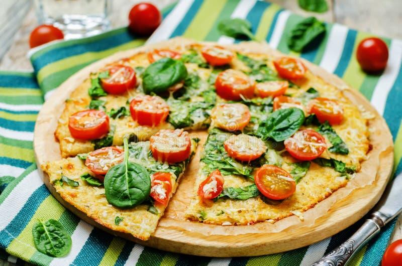 Corteza de la pizza de la coliflor con el tomate y la espinaca imagenes de archivo