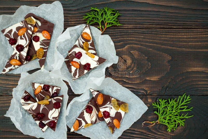 Corteza del chocolate del día de fiesta con las frutas y las nueces secadas en un fondo de madera oscuro Visión superior Receta d fotografía de archivo libre de regalías