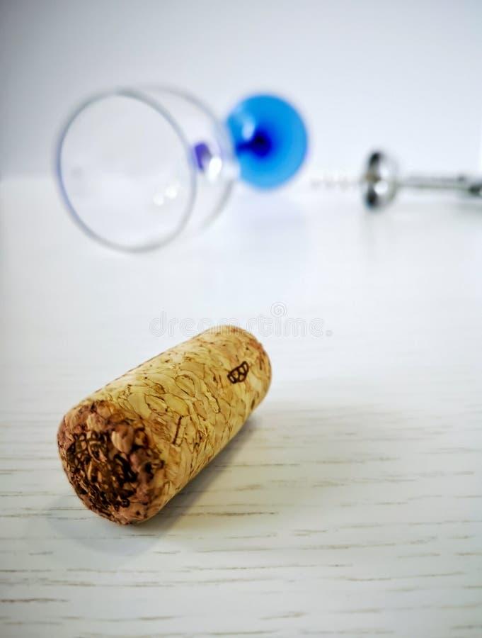 A cortiça do vinho está encontrando-se em uma tabela de madeira branca No fundo, em um corkscrew do metal e em um vidro virado co foto de stock
