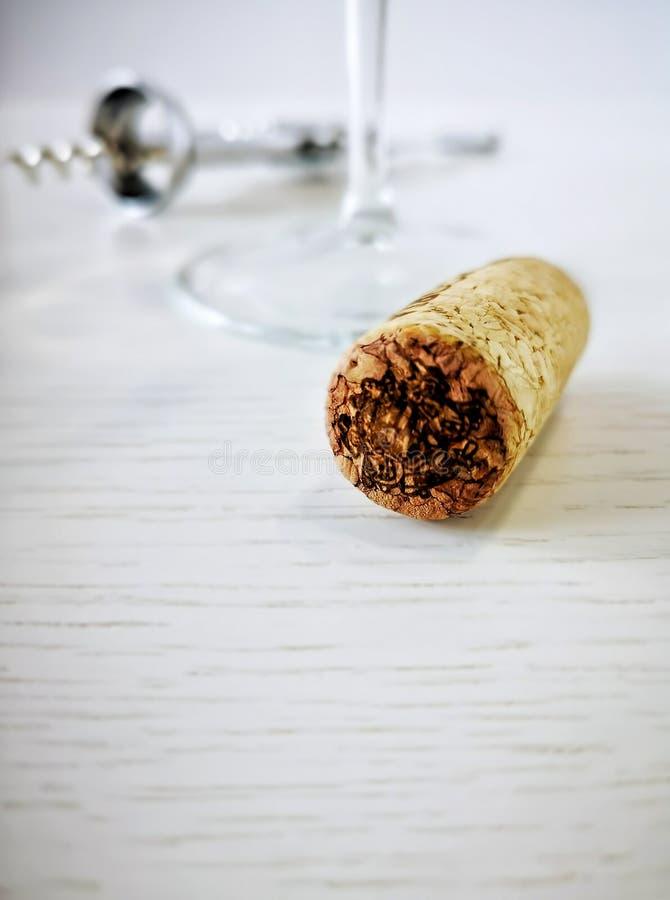 A cortiça do vinho está encontrando-se em uma tabela de madeira branca No fundo, em um corkscrew do metal e em um vidro virado co foto de stock royalty free