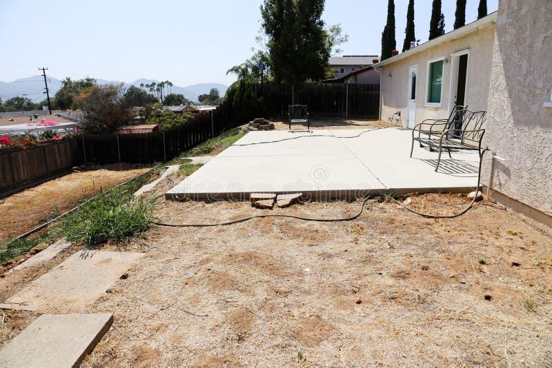 Cortile con la lastra del patio e le erbacce e la casa dello stucco immagine stock libera da diritti