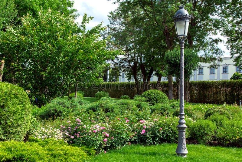 Cortile del giardino con una posta di illuminazione e una lanterna nel retro stile fotografia stock