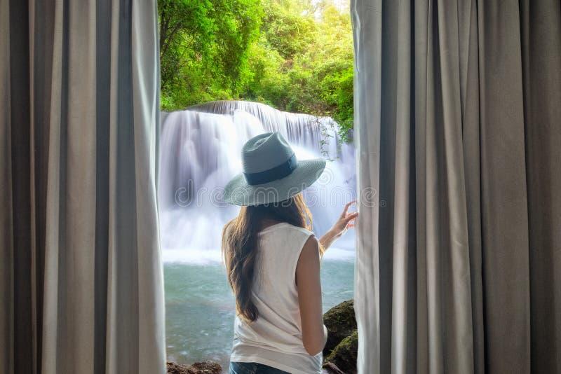 Cortina abierta de la mujer joven para ver fluir hermoso de la cascada natural fotografía de archivo