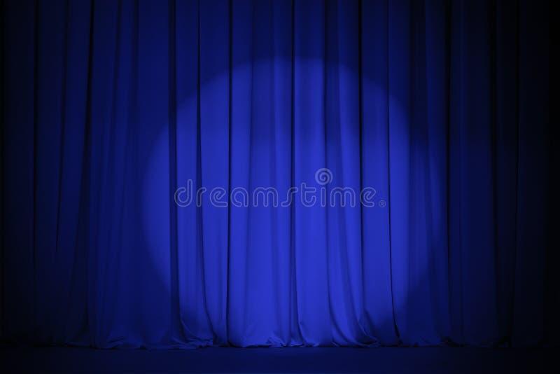 Cortina azul do teatro com ponto claro imagens de stock royalty free
