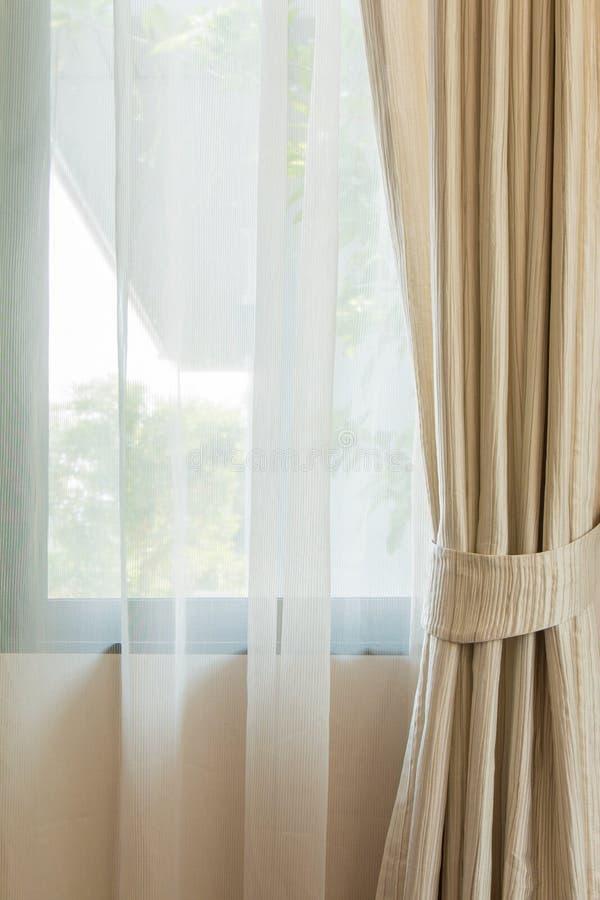 Cortina beige por la ventana fotografía de archivo
