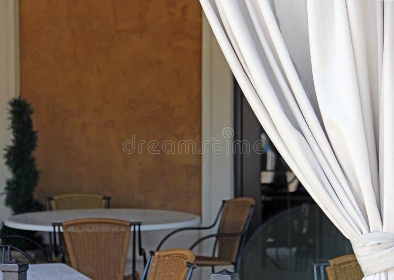 A cortina branca puxou para convidar um para esvaziar a tabela de jantar exterior fotos de stock royalty free