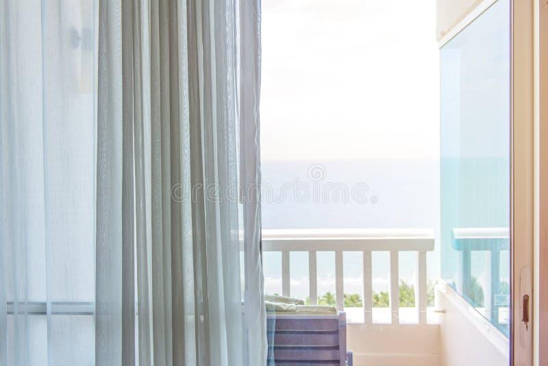 cortina levemente aberta na sala confortável com parte traseira da opinião do mar fotos de stock