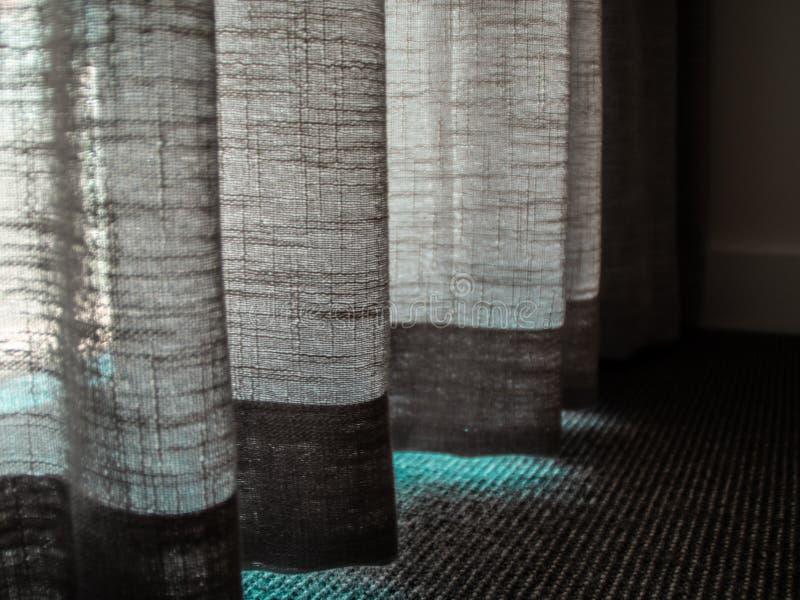 Cortina translúcida de la tela en el cuarto de la moqueta fotos de archivo