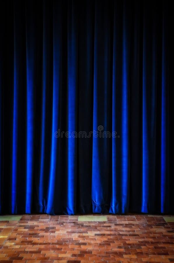 Cortinas azules coloridas de la etapa y piso tejado foto de archivo