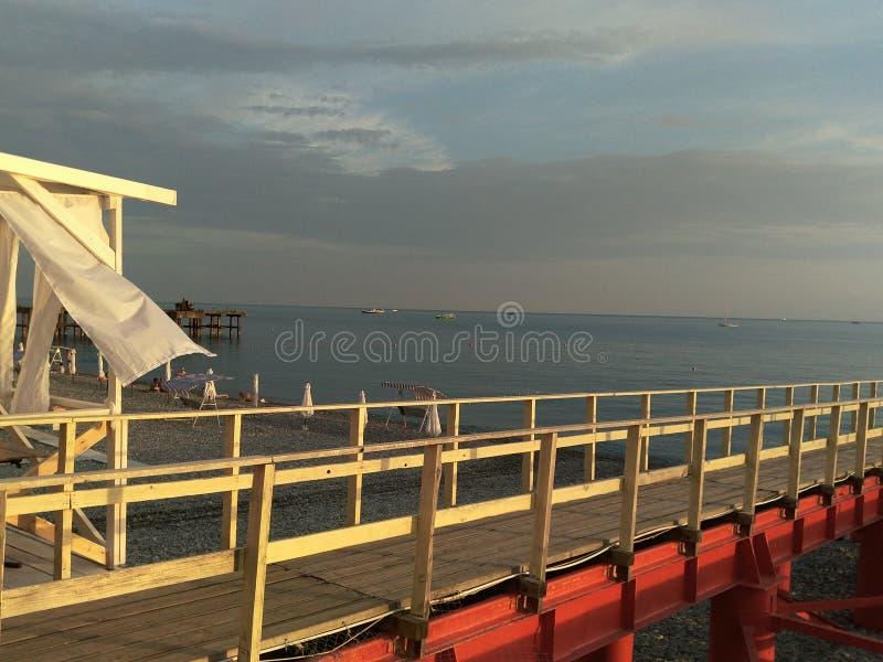 Cortinas blancas en el viento contra el mar y el puente rojo imagen de archivo