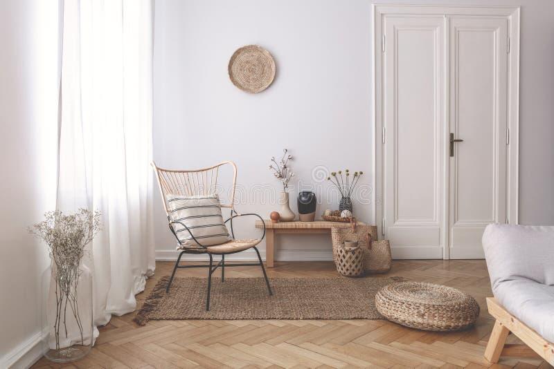 Cortinas blancas escarpadas en la ventana de un interior blanco de la sala de estar con una almohada rayada, de lino en una silla foto de archivo libre de regalías