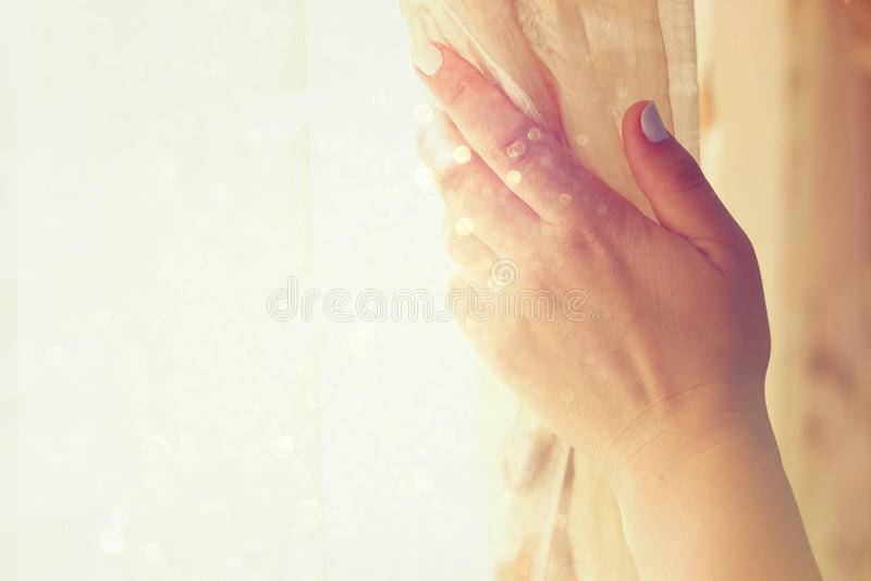 Cortinas de abertura da mão da mulher em um quarto a explosão da luz natural filtrou a imagem com foco seletivo fotos de stock