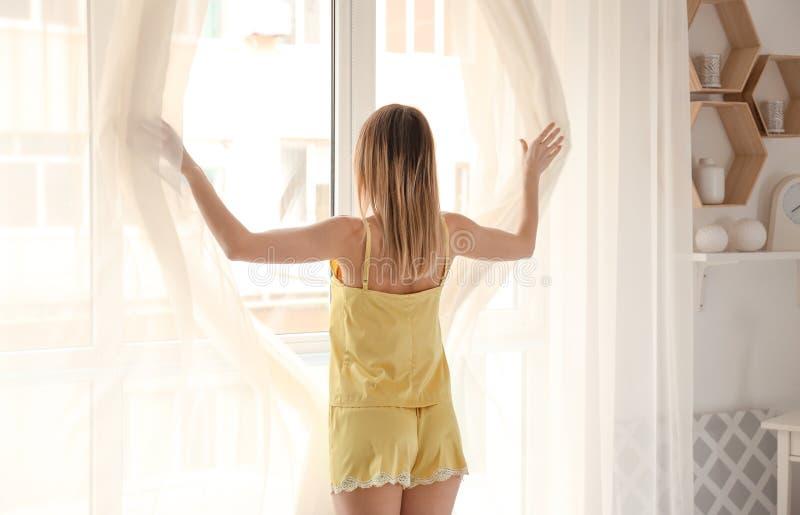 Cortinas de abertura hermosas de la mujer joven por mañana fotografía de archivo libre de regalías