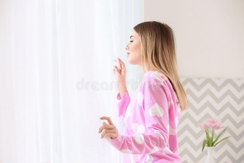 Cortinas de abertura hermosas de la mujer joven por mañana fotografía de archivo