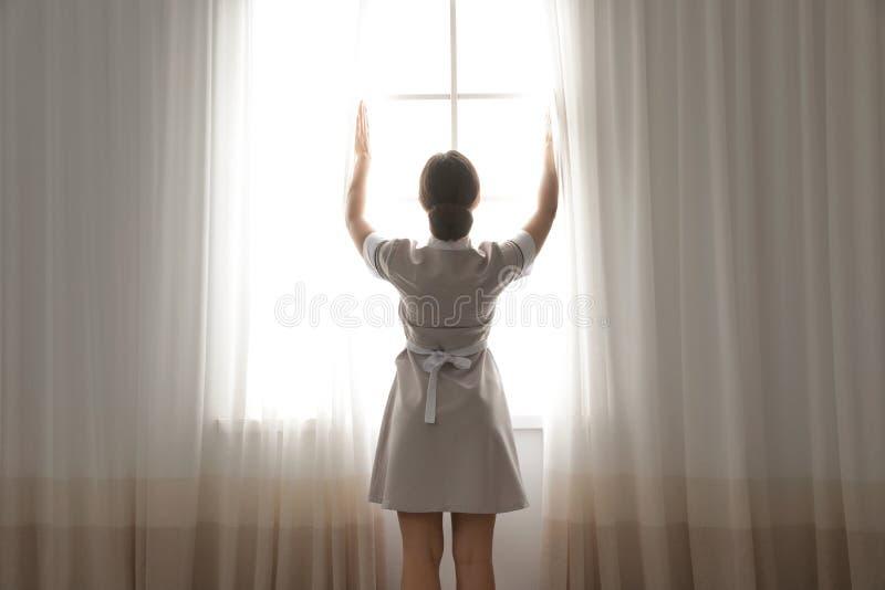 Cortinas de abertura jovenes de la criada en hotel fotos de archivo